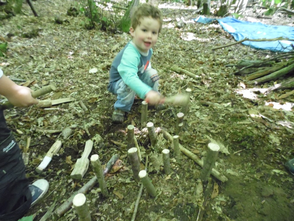 Hammering sticks into the ground to make houses for animals